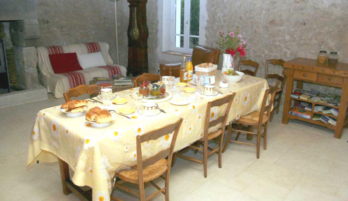 La salle à manger est spacieuse, les pierres et les poutres d'origine y sont mises en valeur.
